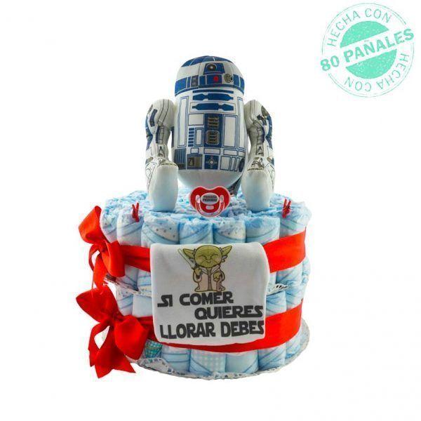 """Tarta de pañales Star Wars para niña. Tiene dos pisos de pañales sujetos por lazos de color rojo. Además lleva un body para bebés recién nacido con el mensaje """"si comer quieres, llorar debes"""" y el dibujo de Yoda (personaje de Star Wars). Arriba de la tarta hay un peluche grande de otro personaje de Star Wars, R2D2 y también tiene un chupete de color rojo con el mensaje """"Pequeña padawan"""""""