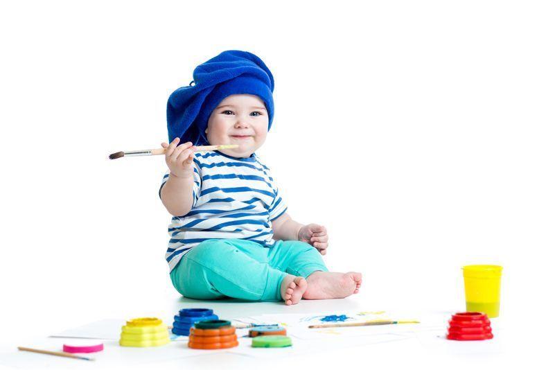 Bebé con gorro azul, sentado con pincel y pinturas