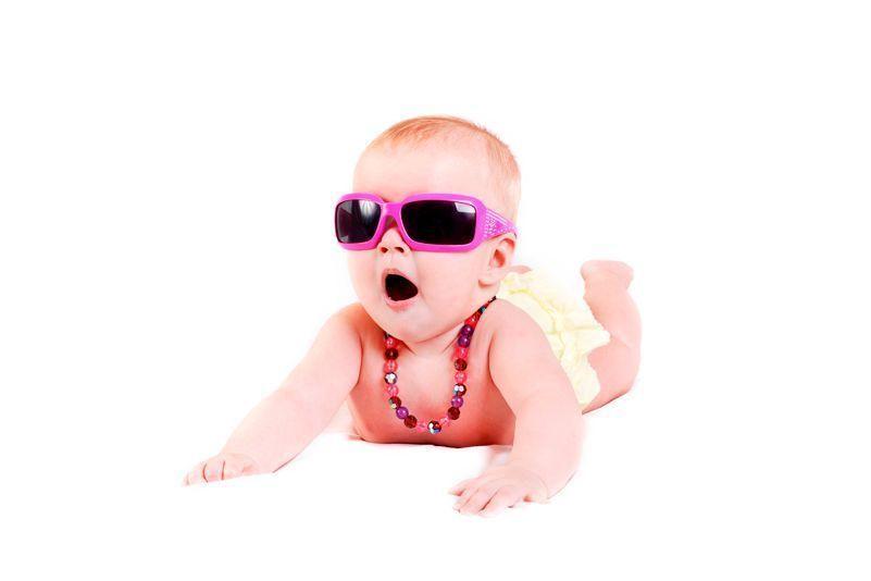 Bebé tumbada con gafas de sol y collar de perlas
