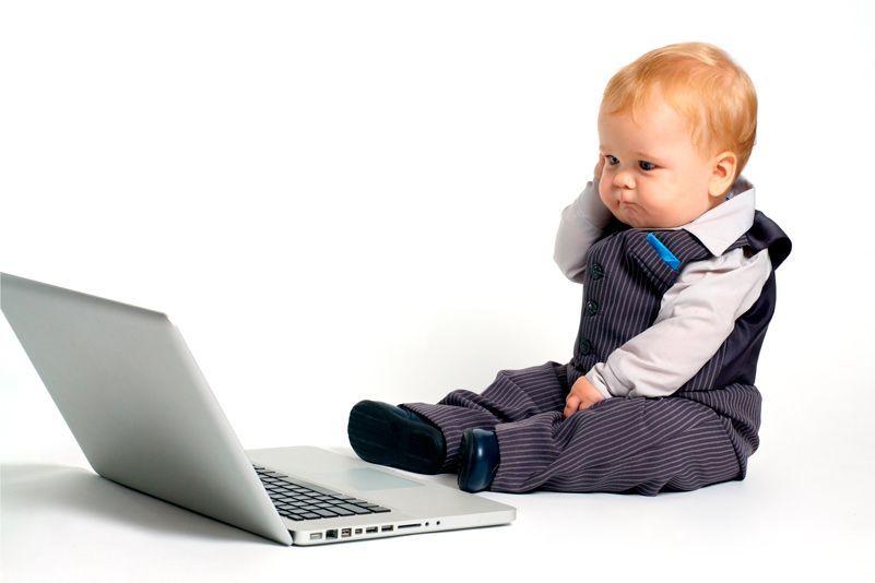 Bebe en traje sentado con un portátil