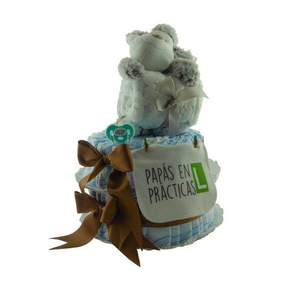 """Tarta de pañales para bebé. Tiene 2 pisos de pañales los cuales están sujetos y decorados por lazos de color marrón. Lleva colgado un babero con el mensaje """"papás en prácticas"""" y un chupete turquesa con el mensaje """"no digo ni pío"""". Encima de la tarta hay un peluche de una oveja sujetando una manta para bebé de color blanco con estrellas grises"""