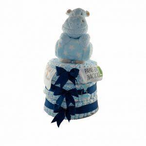 """Tarta de pañales azul claro para niño con 120 pañales repartidos en 3 pisos. Tiene un peluche grande de hipopótamo con una manta de color azul claro, un body de algodón 100% con el mensaje """"papás en prácticas"""" y un babero con el mensaje """"bollito recién hecho"""" además de llevar un chupete de color azul."""