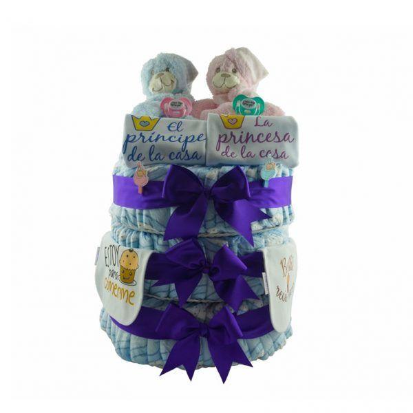 """Gran tarta de pañales para mellizos o gemelos, niño y niña. La tarta lleva 120 pañales repartidos en 3 pisos. Es una tarta muy completa ya que lleva 2 doudous, uno rosa y otro azul, 2 chupetes de diferentes colores con mensaje divertido el cual también se puede personalizar con los nombres de los bebés si se desea. También incluye 2 bodies de algodón para bebés de 0 a 3 meses. Llevan grabados """"El principe de la casa"""" para el niño y el otro body """"La princesa de la casa"""" para la niña. Por último también incluye 2 baberos de algodón con mensajes diferentes para cada uno de los bebés"""