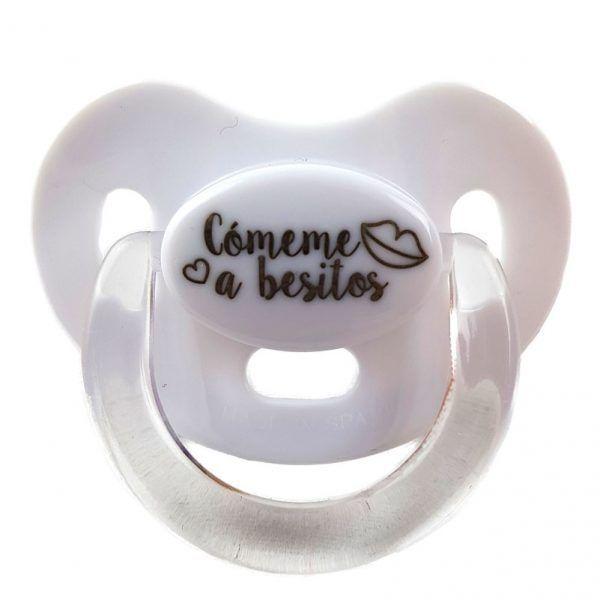 Chupete blanco para bebé con el mensaje Cómeme a besitos