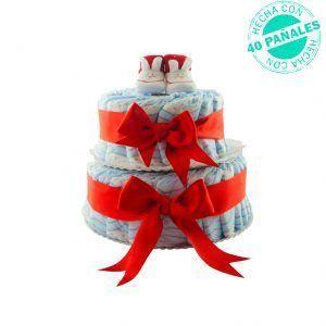 Tarta de pañales económica para recién nacidos. Es una tarta hecha con 40 pañales ordenados en 2 pisos y sujetos y decorados por lazos de color rojo. Arriba de la tarta hay un par de patucos con la cara de un conejo