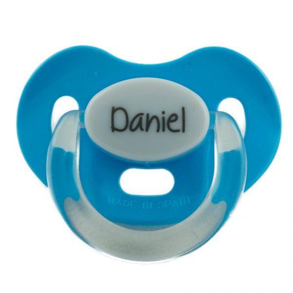 Chupete azul claro con tetina de silicona para bebés de 0 a 6 meses. Está personalizado con el nombre del bebé