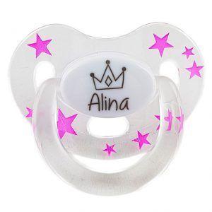 Chupete para bebés de 0 a 6 meses, transparente con estrellas fucsias y el dibujo de una corona grabado en el centro junto con el nombre Alina