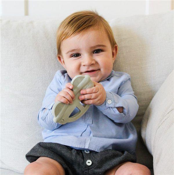 Bebé sentado sujetando el mordedor con forma de coche entre sus manos